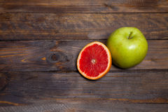 Fresh green apple and juicy cut grapefruit on wooden background Stock Image