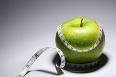 Fresh green apple with measure tape Royalty Free Stock Image