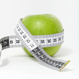 Fresh green apple with measuring tape Stock Images