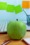 Fresh green apple on office desk. Concept of healthy snack and/or diet during working hours Royalty Free Stock Photo