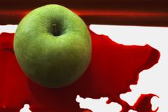 Fresh green apple in a pool of red blood Royalty Free Stock Photos