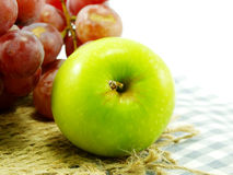 Fresh green apple and red grapes on tablecloth Royalty Free Stock Images