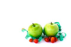 Fresh green apple and red tometos with measuring tape on white b Royalty Free Stock Photo