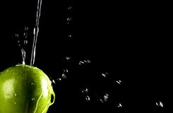 Fresh Green Apple with Water Splash. Healthy Fruit With Clear Water Droplets with Isolated Black Background Stock Photo