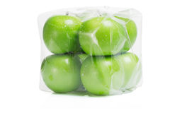 Fresh green apples. In transparent packing on white background Stock Photo