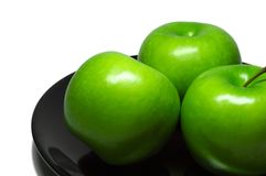 Fresh green apples on a black plate. White background. royalty free stock photos