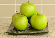 Fresh green apples in flat plate on counter top Royalty Free Stock Photography