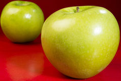 Fresh green apples. Two green apples on red table royalty free stock images