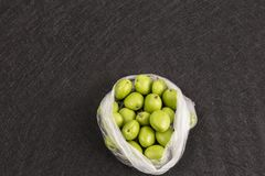 Fresh green apricots in package on black background.  Royalty Free Stock Photography