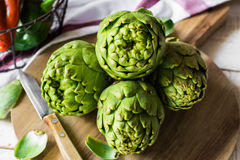 Fresh green artichokes on cutting board top view with peeled off leaves, Italian sweet peppers in basket Royalty Free Stock Photo