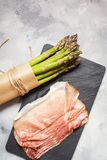 Fresh green asparagus and bacon on a rustic concrete table. Top view stock image