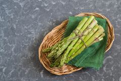 Fresh green asparagus in basket. Fresh green asparagus on green linen cloth in basket. Bunch of raw asparagus sprouts. Healthy food, vegetarian dieting concept Stock Photo