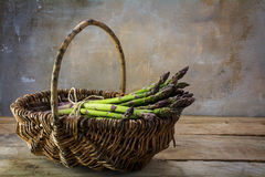 Fresh green asparagus in a basket on a rustic wooden table in fr. Ont of a vintage wall with copy space in the background, selected focus Stock Image