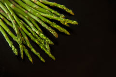 Fresh green asparagus  on black. Food background Royalty Free Stock Photos