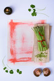 Fresh green asparagus and black tomato kumato on wooden board. Top view, copy space. Stock Photography