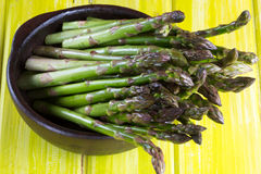 Fresh green asparagus in clay bowl Stock Image