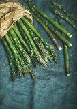 Fresh green asparagus in craft paper bag, copy space. Fresh green asparagus in craft paper bag over dark grey linen table cloth background, top view, copy space Stock Photos