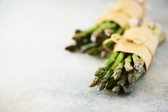 Fresh green asparagus in craft paper on marble background. Banner. Raw, vegan, vegetarian and clean eating concept. Food stock photos