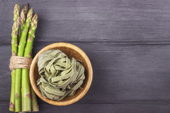 Fresh green asparagus and fettuccine italian pasta in bowl on wo. Oden background Stock Image