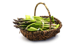 Fresh green asparagus in a harvest basket, isolated with small s Stock Photo