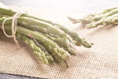 Fresh green asparagus on the old kitchen table and on a napkin royalty free stock images