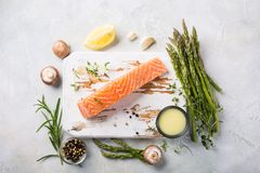 Fresh green asparagus and raw salmon fillet. Overhead shoot with fresh green asparagus, raw salmon fillet, herbs and sauce and old white wooden board. Healthy Stock Photos