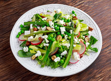 Fresh Green Asparagus salad witch Goat Cheese, peas, radishe, zucchini, lettuce and Hazelnuts. Stock Photos