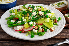 Fresh Green Asparagus salad witch Goat Cheese, peas, radishe, zucchini, lettuce and Hazelnuts. Royalty Free Stock Photos