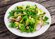 Fresh Green Asparagus salad witch peas, radishe, zucchini, lettuce and Hazelnuts. Royalty Free Stock Images