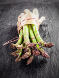 Fresh green asparagus spears. Bundled in brown paper and tied with string displayed with their tips to the camera on a grey textured slate surface royalty free stock photo