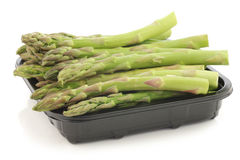 fresh green asparagus tips on a black plastic tray Stock Image