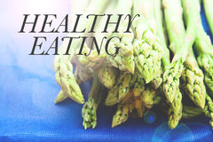 Fresh green asparagus tips on blue background, HEALTHY EATING Stock Images
