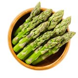 Fresh green asparagus tips in wooden bowl. Sparrow grass shoots. Cultivated Asparagus officinalis. Vegetable with thick stems and closed buds. Isolated macro Stock Photography