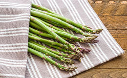 Fresh green asparagus on wooden background with linen cloth Royalty Free Stock Photos
