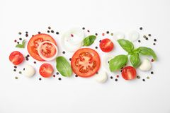 Fresh green basil leaves, tomatoes and mozzarella on white background. Top view stock images