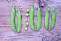 Fresh green beans of peas not like others pods on old wood Stock Image