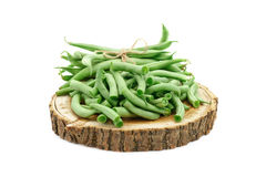 Fresh green beans are on a wooden stump. An isolated object. Royalty Free Stock Image