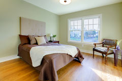 Fresh green bedroom with modern brown bed Stock Images