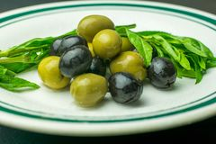 Fresh green and black olives, served on a white porcelain plate royalty free stock photos