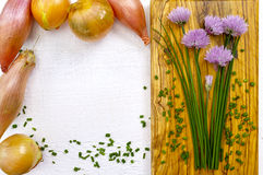 Fresh green blooming chives, shallots and yellow onion. On white and olive wood background Stock Photo