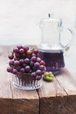 Fresh green  blue grapes and carafe of grape juice  on wooden table Stock Photo