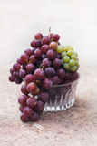 Fresh green and blue  grapes in a crystal vase.  Rustic style. Stock Images