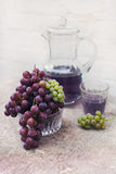 Fresh green and blue grapes on natural textured canvas.A carafe of grape juice Stock Images