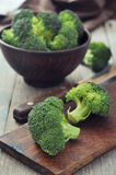 Fresh green broccoli. Bunch of fresh green broccoli in brown bowl over wooden background Stock Image