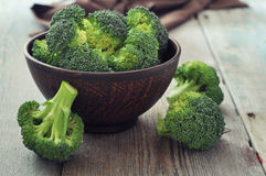 Fresh green broccoli. Bunch of fresh green broccoli in brown bowl over wooden background Stock Photos