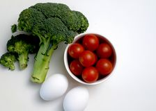 Fresh broccoli, cherry tomatoes and eggs stock photography