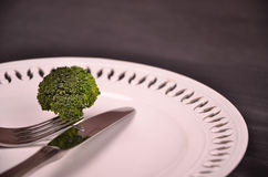 Fresh green broccoli on white plate over wooden background Royalty Free Stock Image