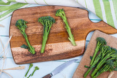 Fresh green broccolini on clipping board Royalty Free Stock Photo