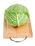 Fresh green cabbage head on wooden chopping board Stock Photo