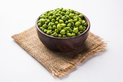 Fresh Green Chickpeas or Chick peas also known as harbara or harbhara. In hindi and Cicer is scientific name, served in a wooden bowl or plate. selective focus stock image